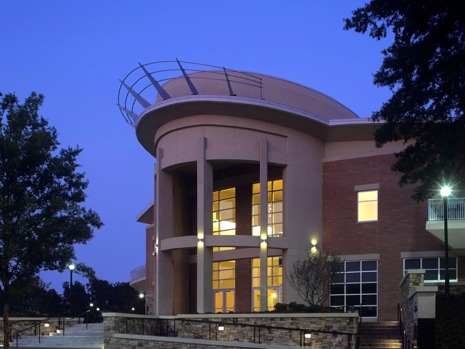 Outside of grand entrance during the evening with lights and floor to ceiling windows with big columns.