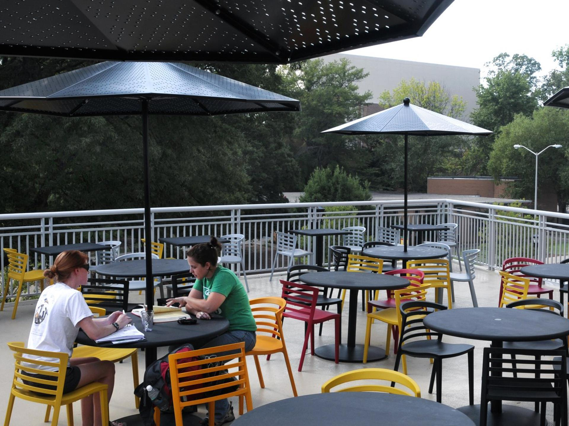 Outside eating area with tables and chairs and umbrellas on outside deck.