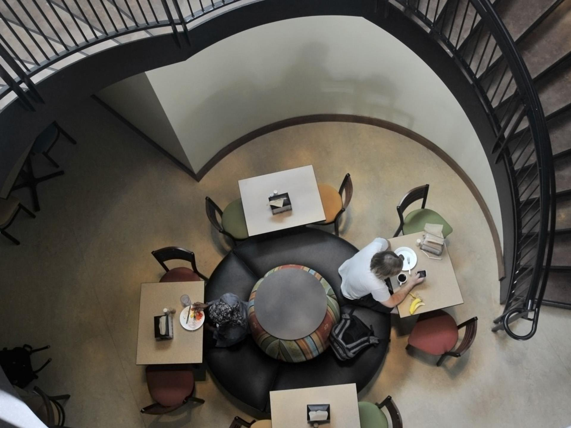 Aerial view of round clouch awith tables and chairs - lounge with spiral staircase.