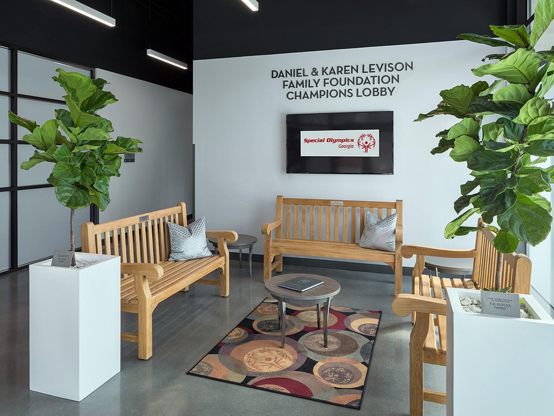 "Sitting area with aerial rug, plants, and signage saying ""Daniel & Karen Levison Family foundation Champions Lobby"""