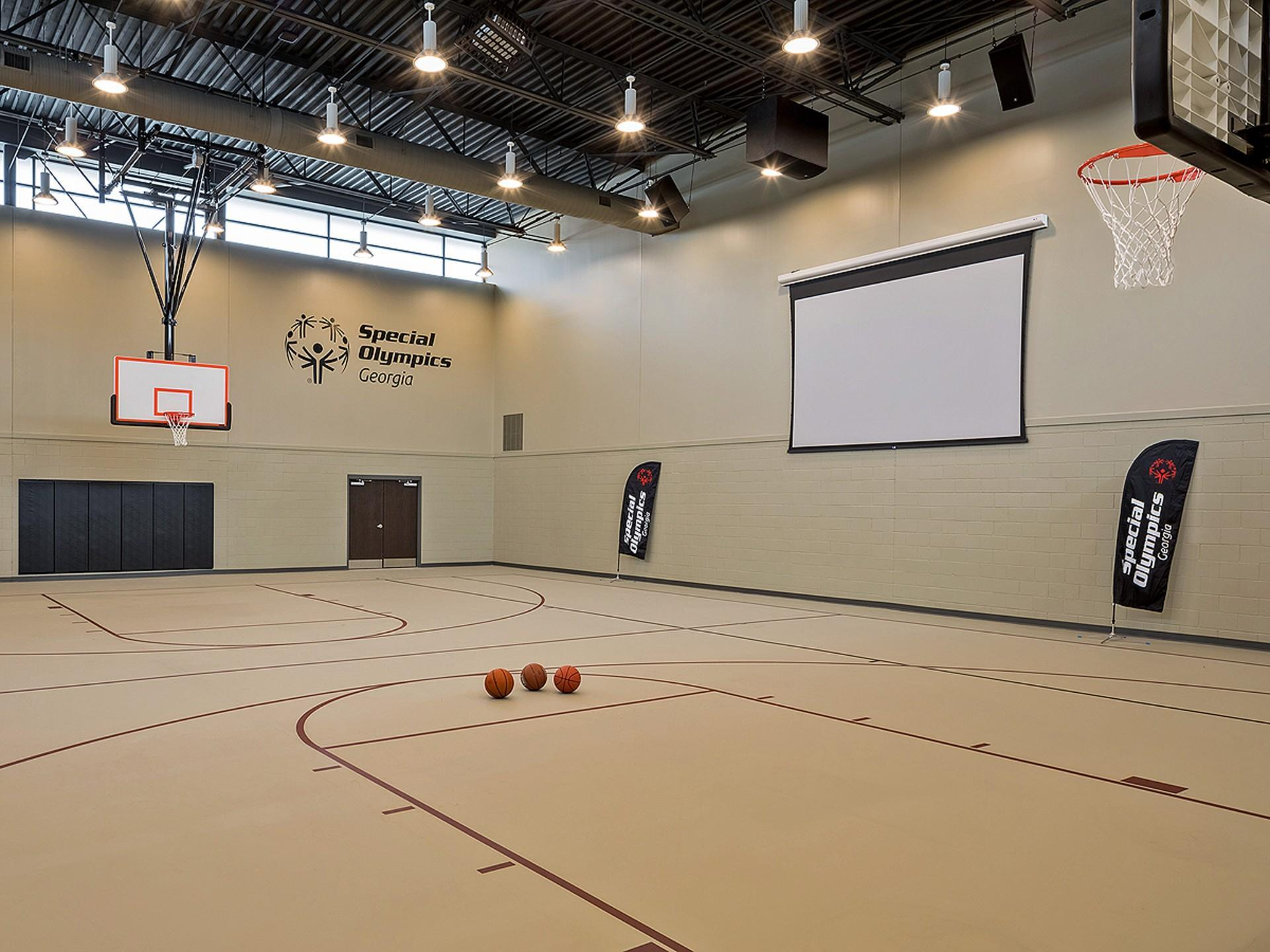 Empty basketball court with lights on, three basketballs center court, and projection screen