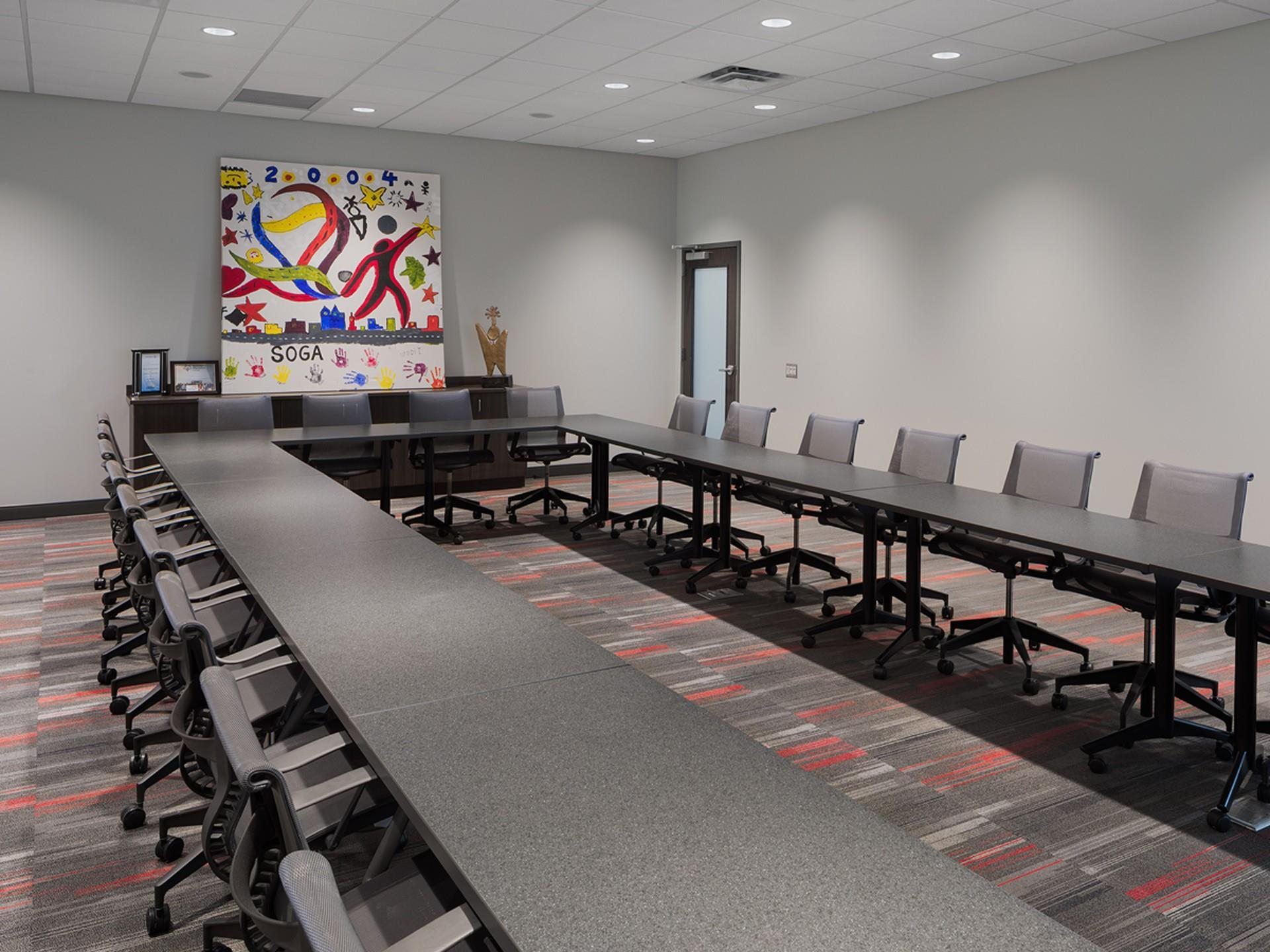 Long u-shaped tables in conferences room with special olympics Georgia colorful signage
