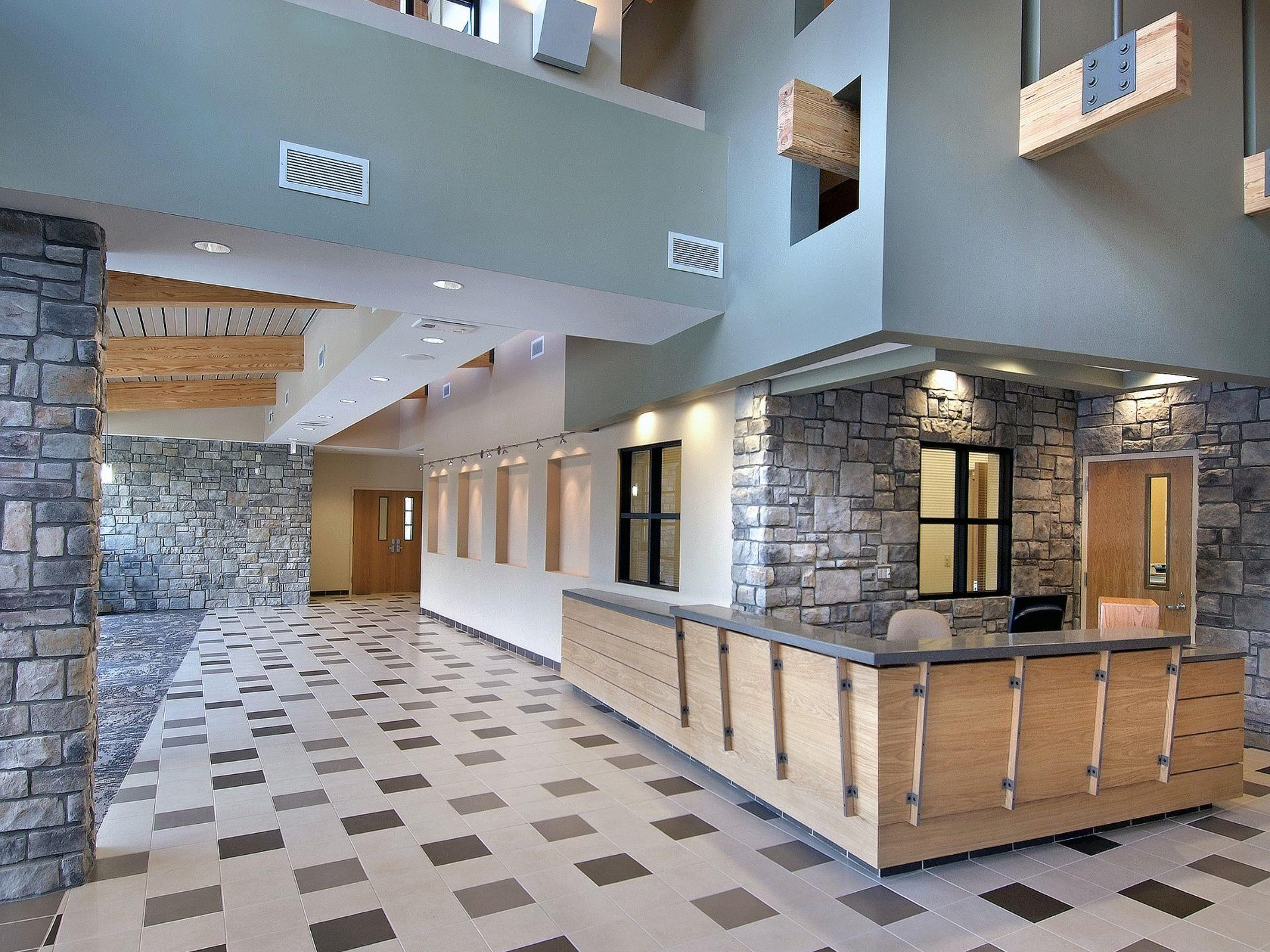 Interior photos of wood front desk surrounded by stone walls and open atrium