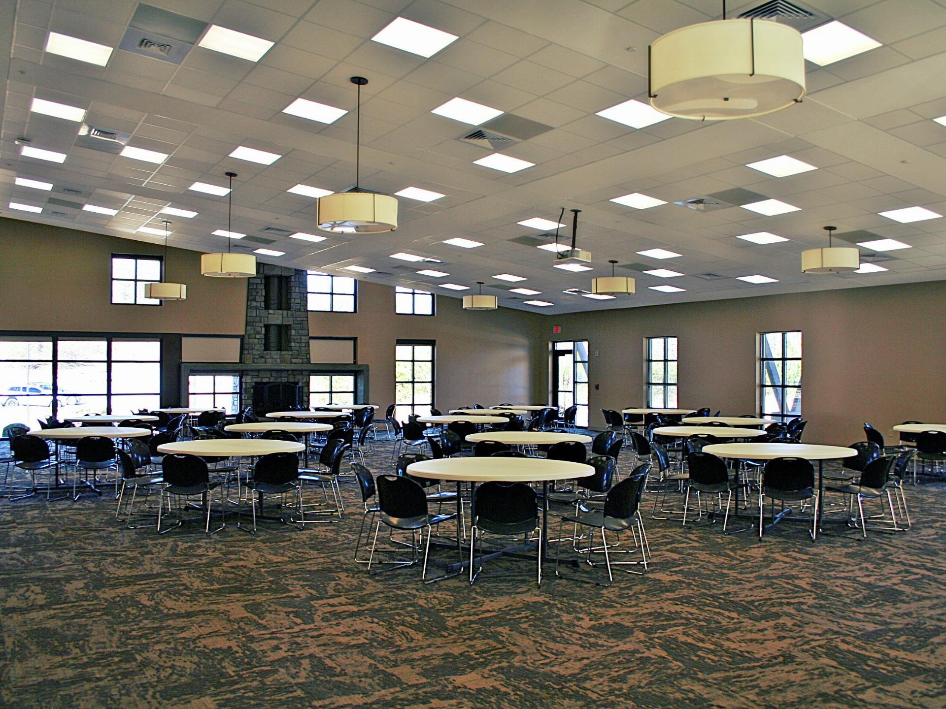 Large community center with round tables and chairs and fire place, lite by drop tile lights and several hanging fixtures