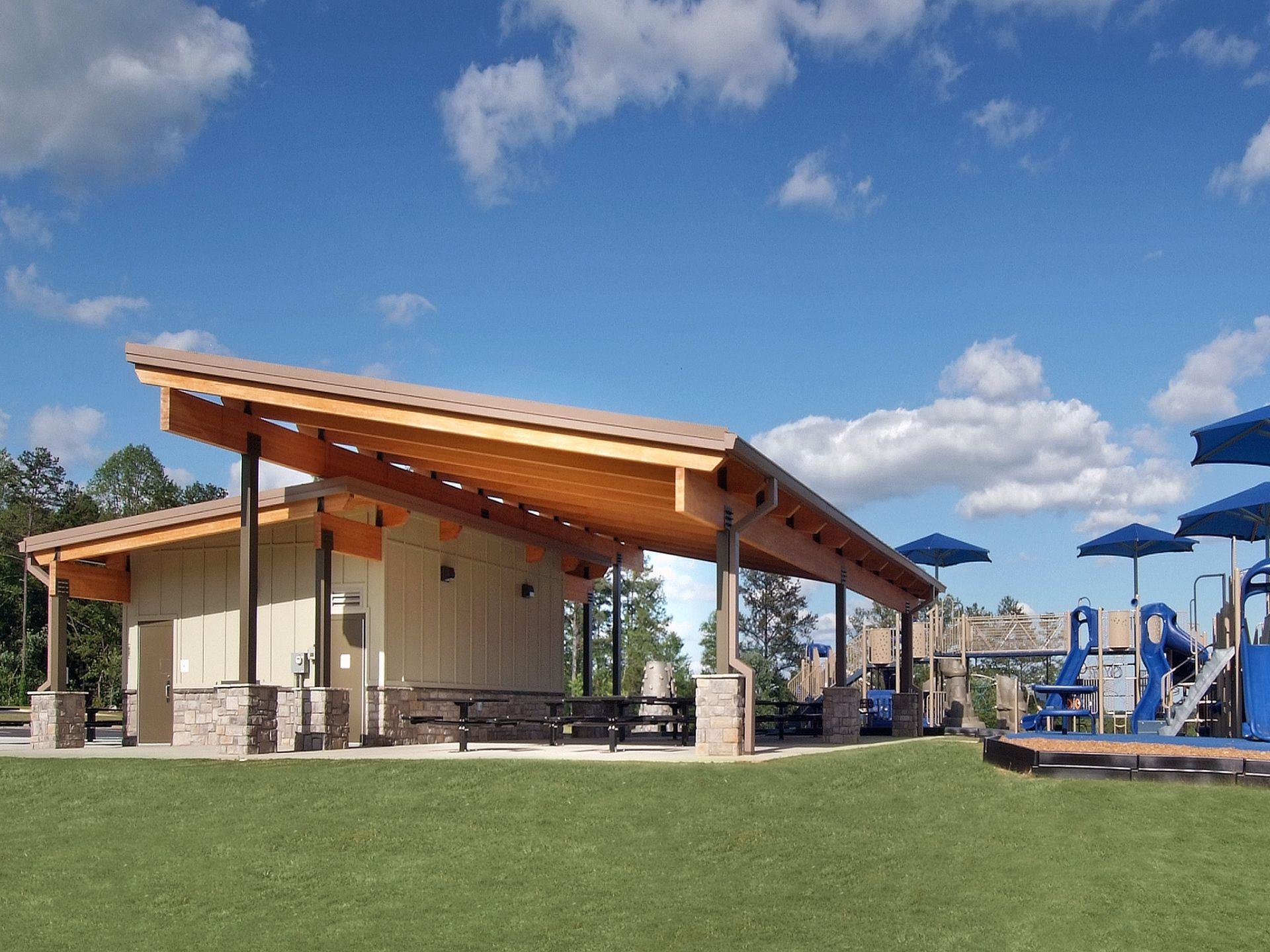Outside amenities include craftman style restrooms with picnic pavilion area covered by slanted wood beam structure and playground area on grass