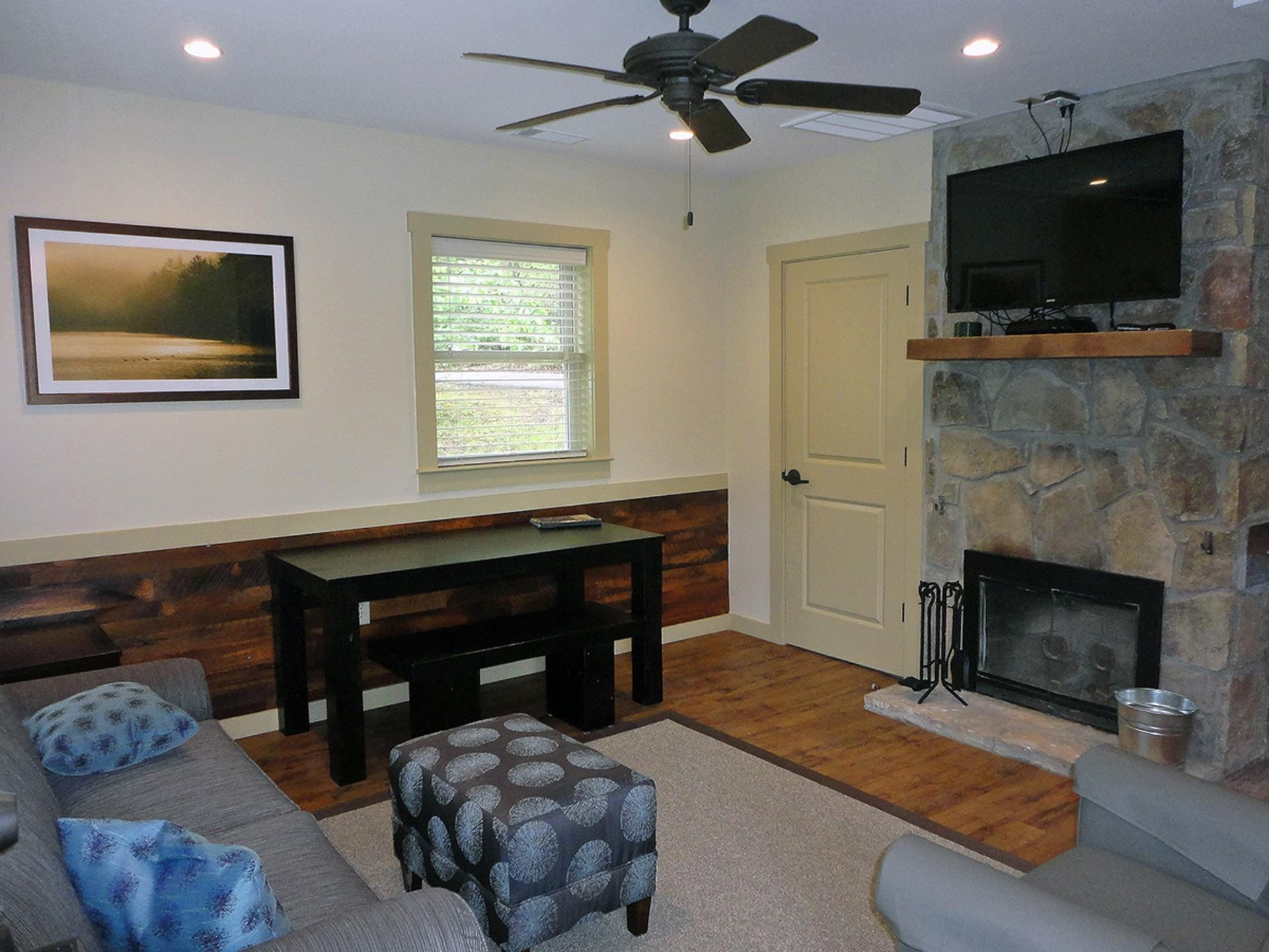 Inside view of cabin with stone fire place and tv and couch with ottoman and table and chairs with natural light.