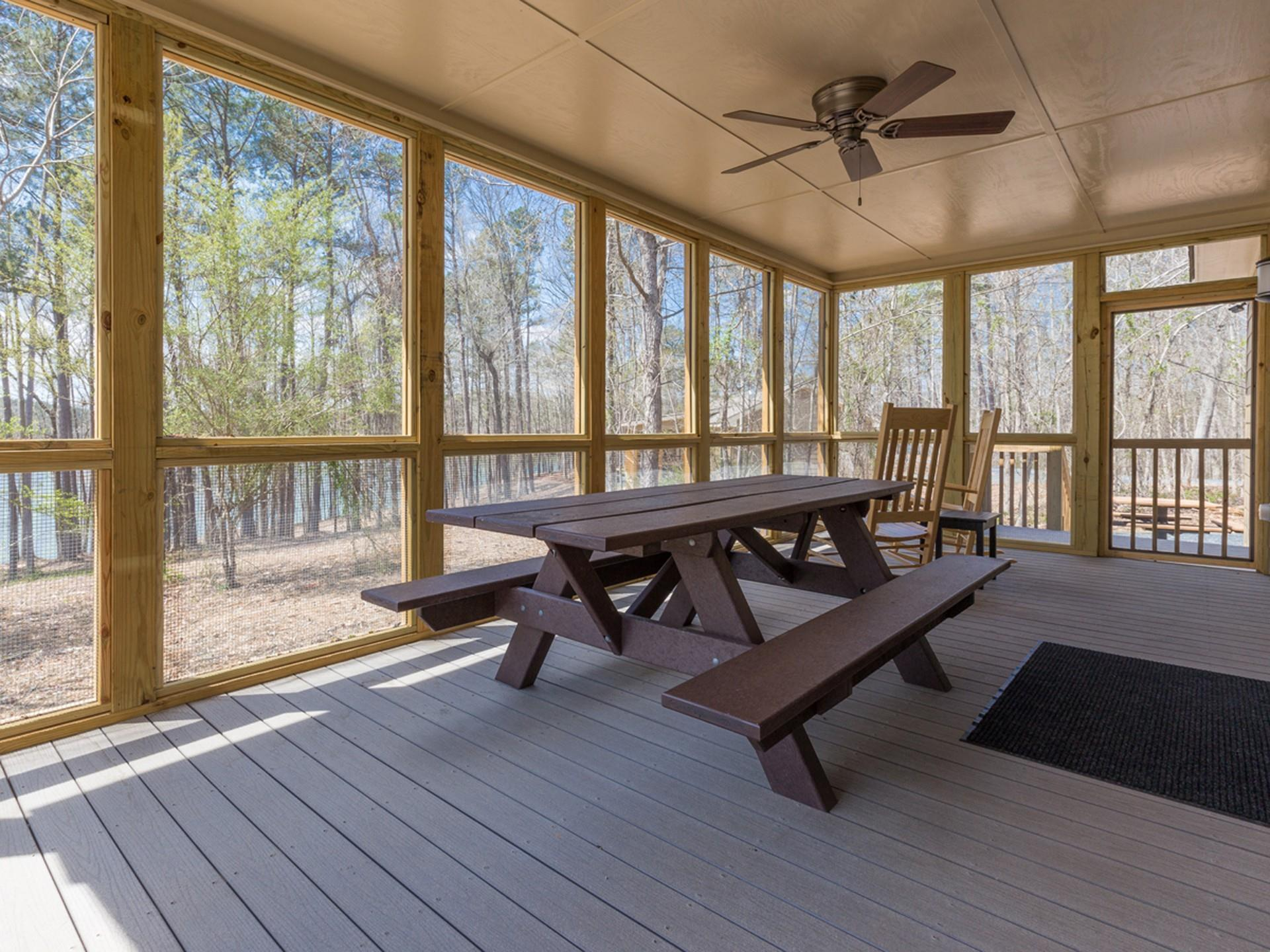 Picnic table on outside screened in porch with ceiling fan  and rocking chairs.