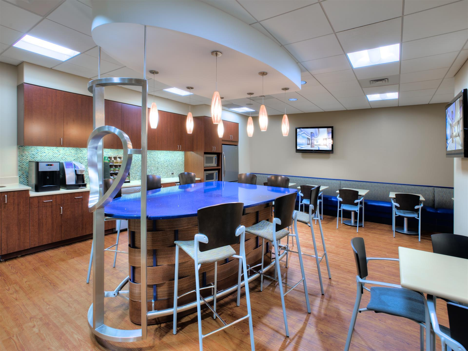 high top table with blue counter and modern hanging lights with stools and kitchen cafe area with tables and chairs