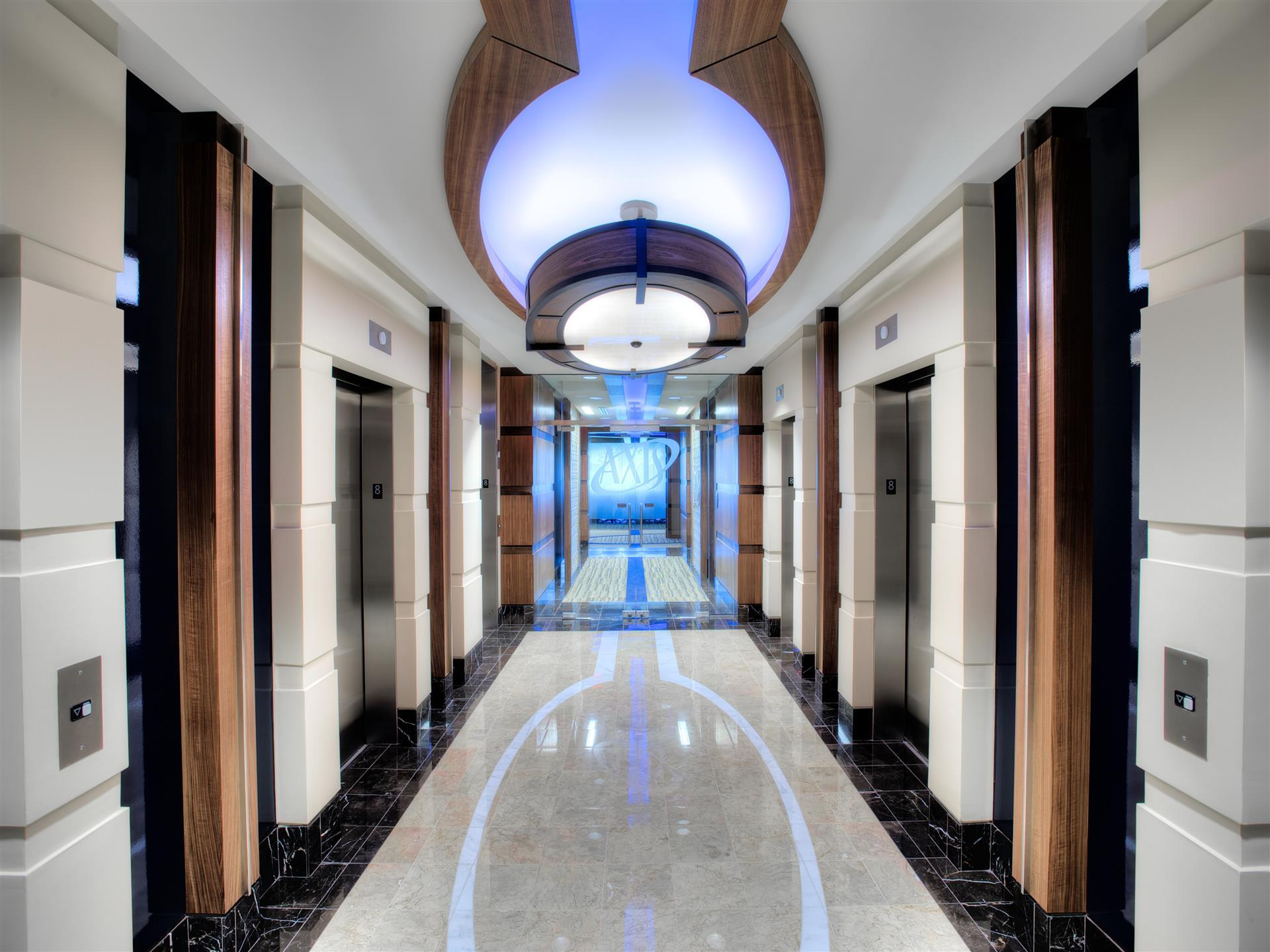 hallway with marble floors and bi overhead light on ceiling withblue aura and frosted glass doors with elevators