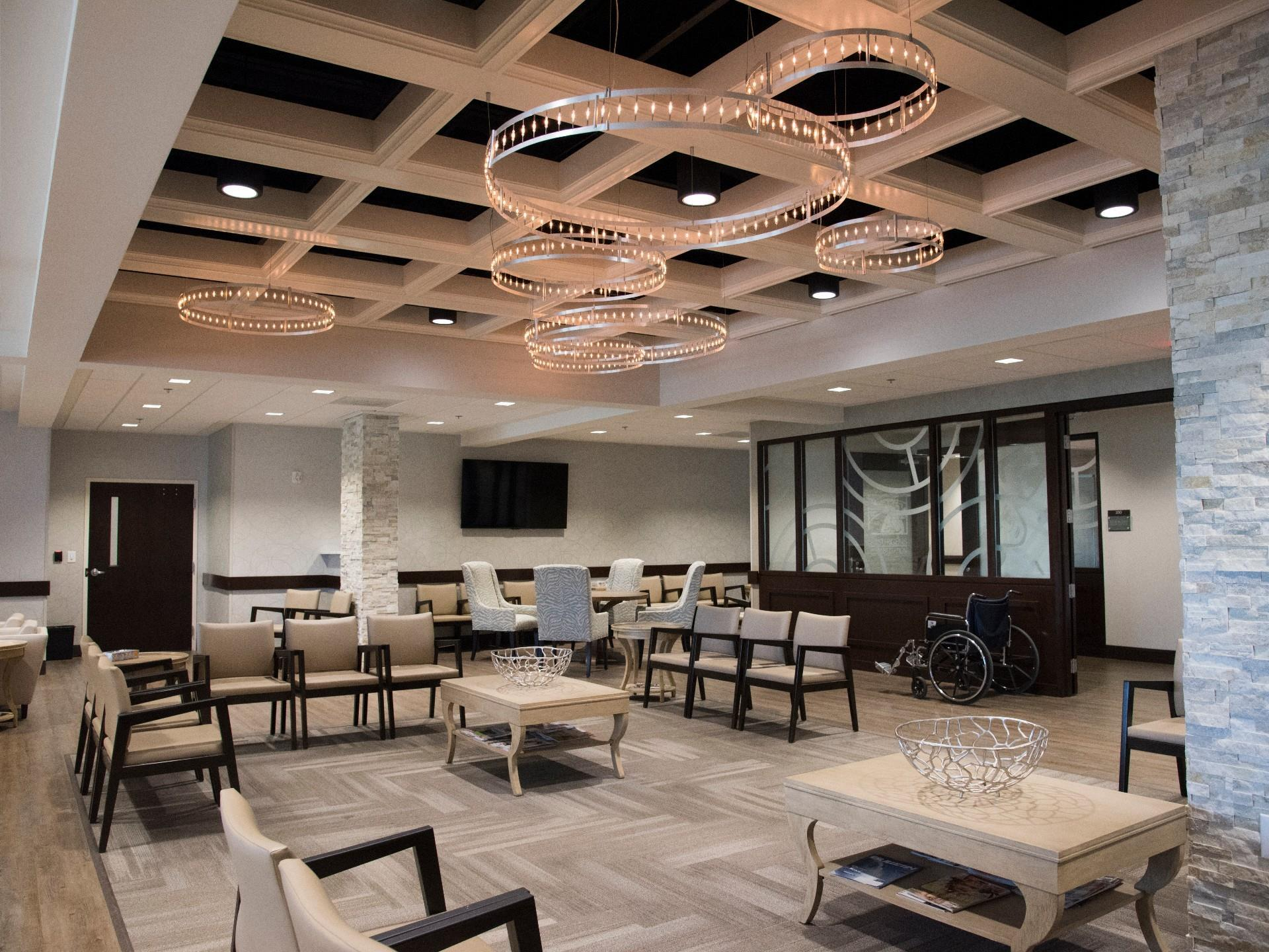 open lobby with decorative chandeliers from ceiling and tables with chairs waiting area