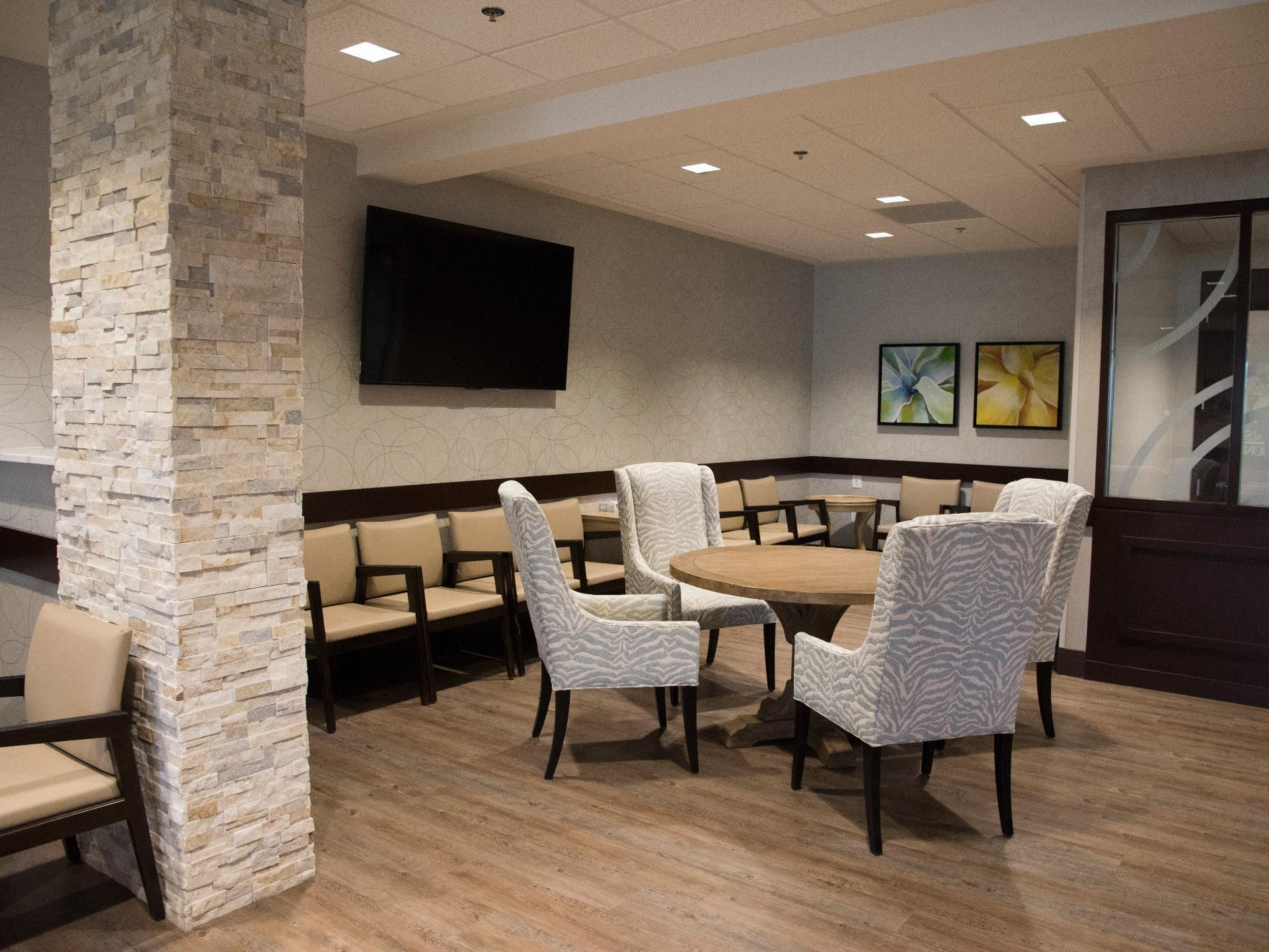 stone column inside with table and comfy arm chairs with flat screen tv mounted on wall and mor echairs against wall