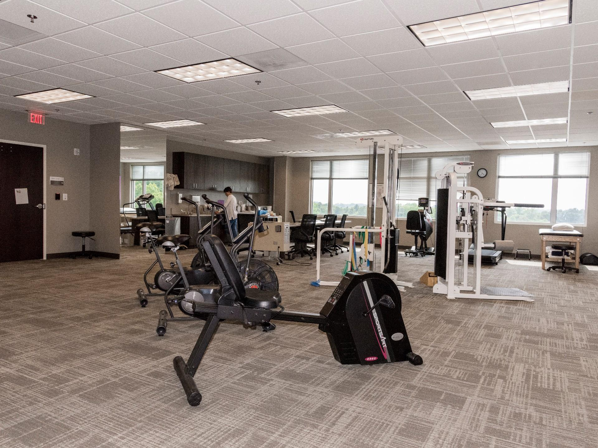 indoor gym with big open light windows and workout equipment