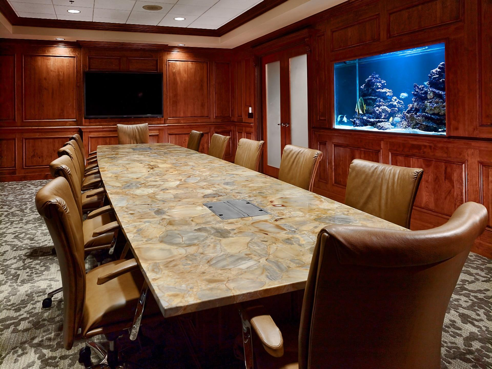 flooor to ceiling wood panels with big long conference room table and leather office chairs with fish tank built into wall