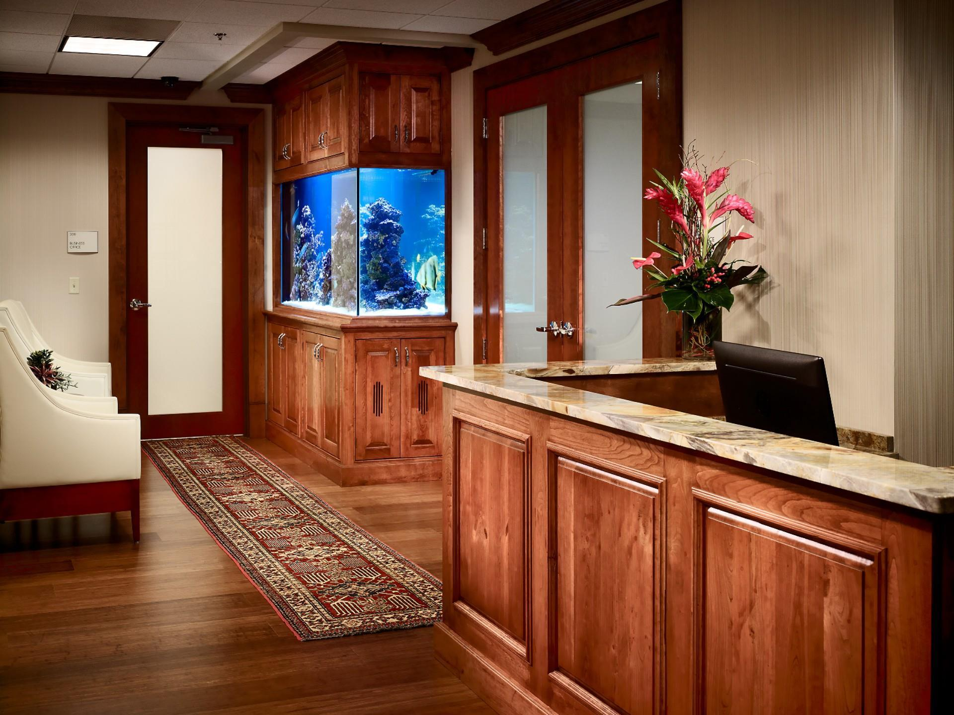 ornate entry way with wood paneled walls and desk with marble top with fish tank in wall