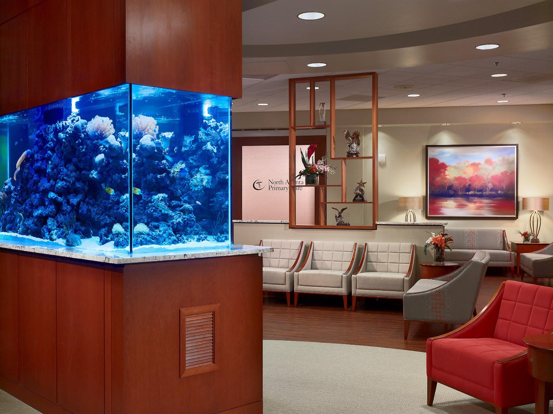 view with fish tank and wood paneling with arm chairs and modern decoritve scultpure with plants on shelves waiting area