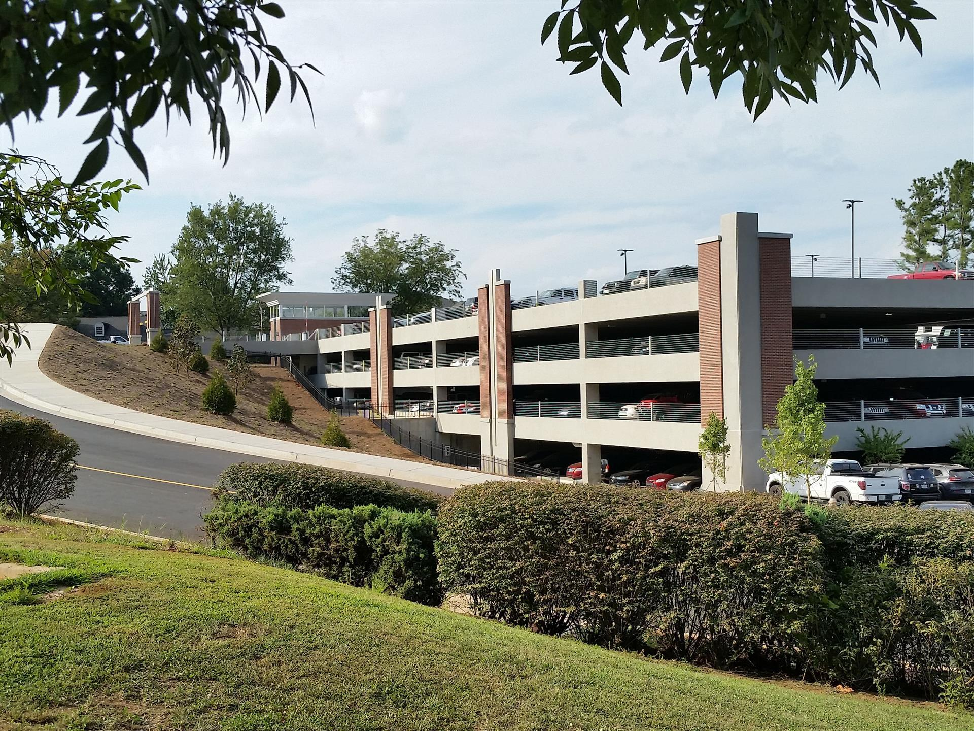 parking garage on hill with brick accents and lots of shrubbery
