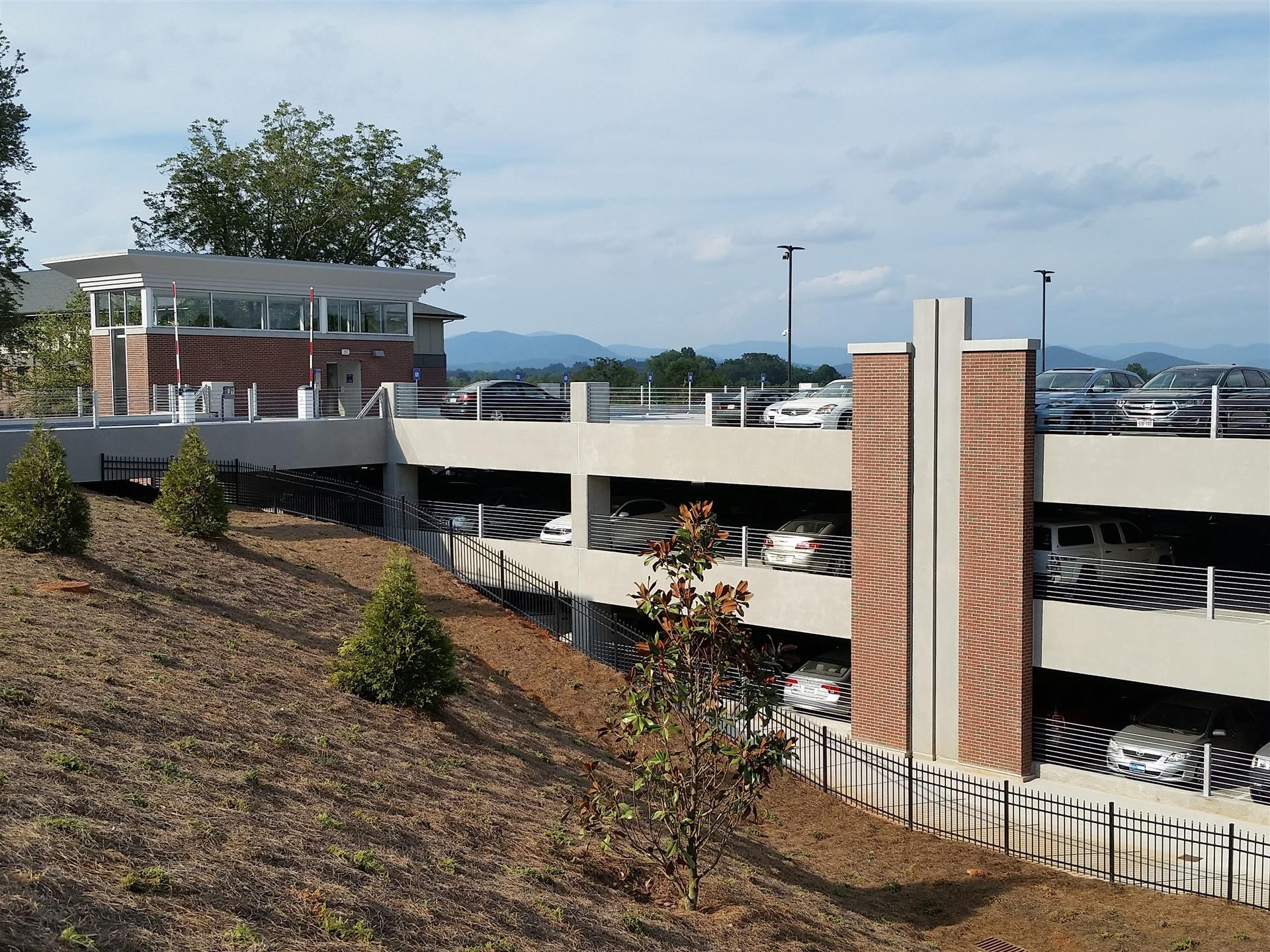 parking garage on hill with brick accents and lots of shrubbery and iron fence going down hill
