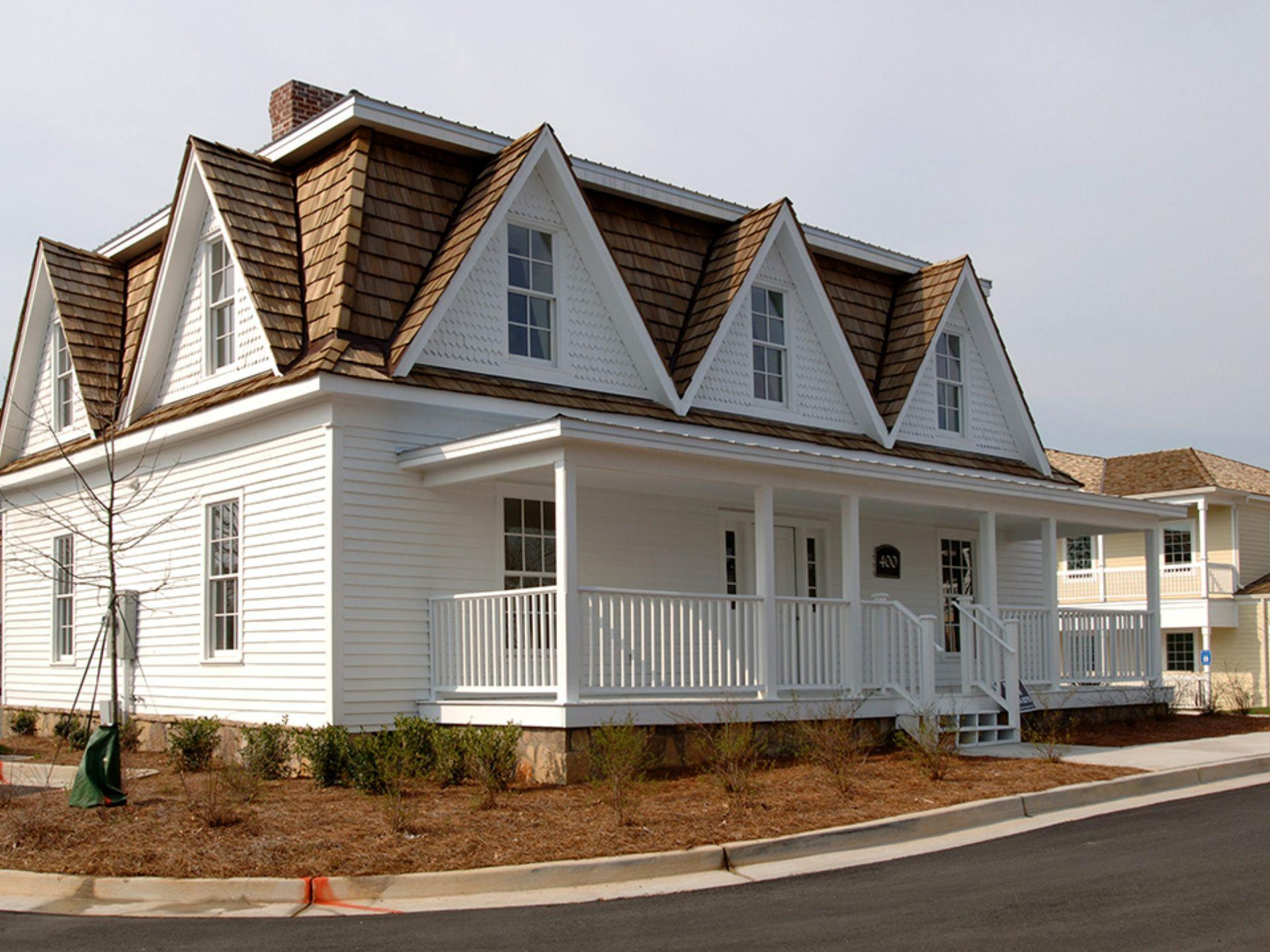 outside of white cottage looking house with widows peak windows on second floor