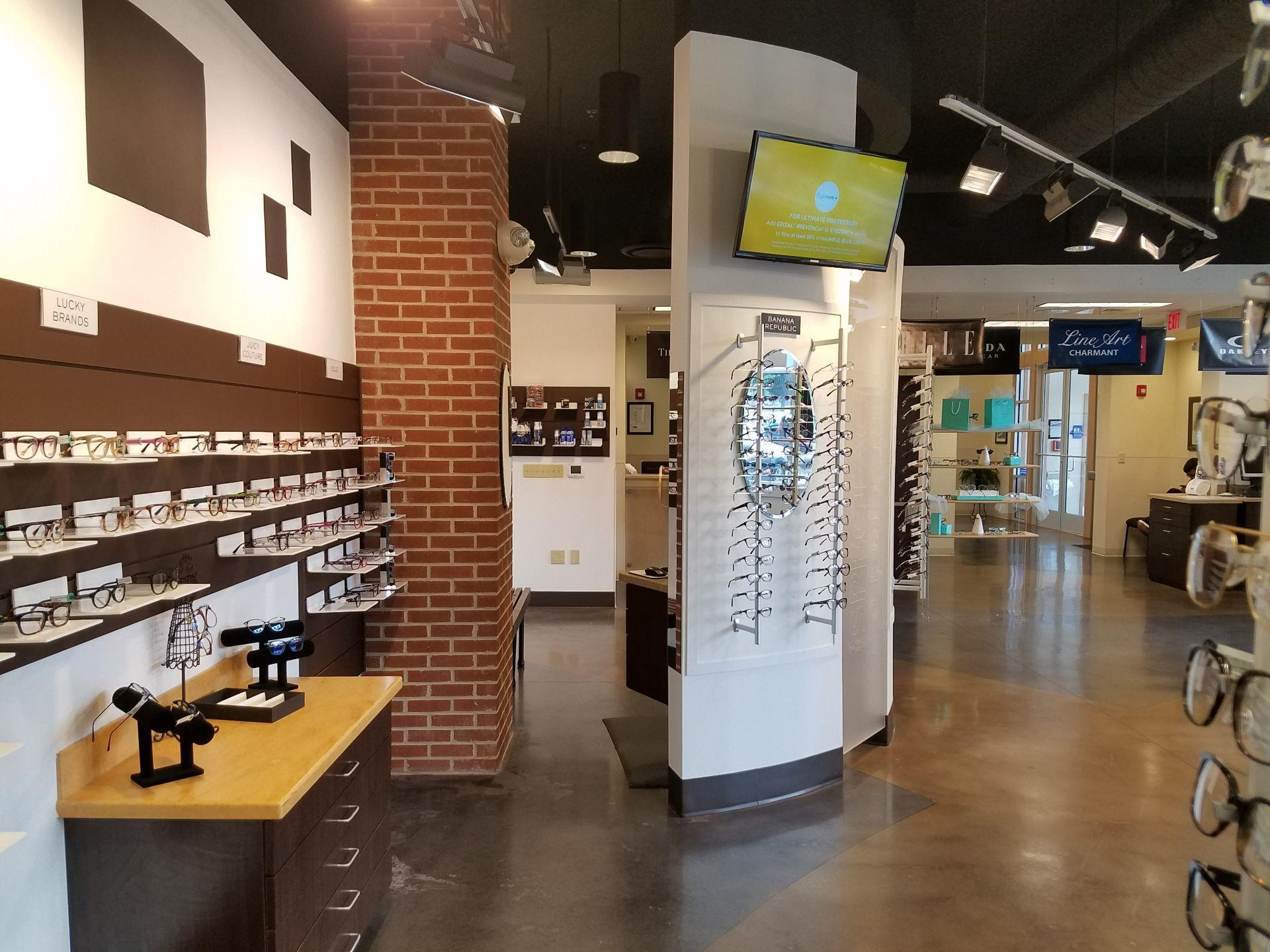 inside of store with glasses on display and flat screen on waalll