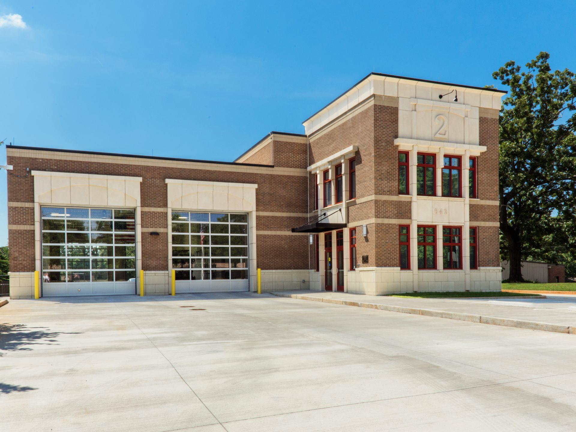 exterior photo of a fire station showing driveway and 2-bay garage