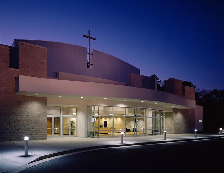Exterior dusk photo of front entrance of church. White front, light brick, cross above entrance