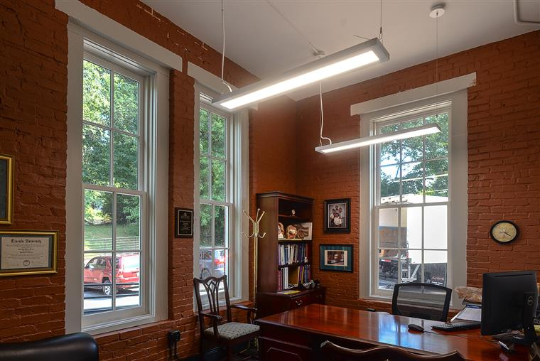 College administration office with 3 windows, desk, pictures hanging, drop lights