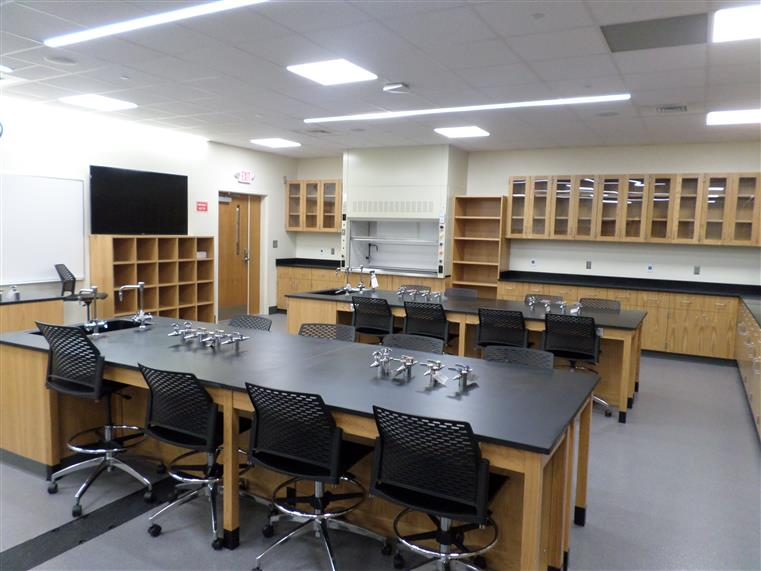 Instructional science lab with work desk and shelves along the wall