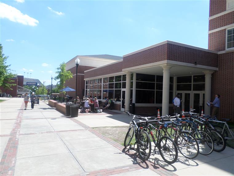 Exterior of university building with bikes in the foreground and students seated outdoors