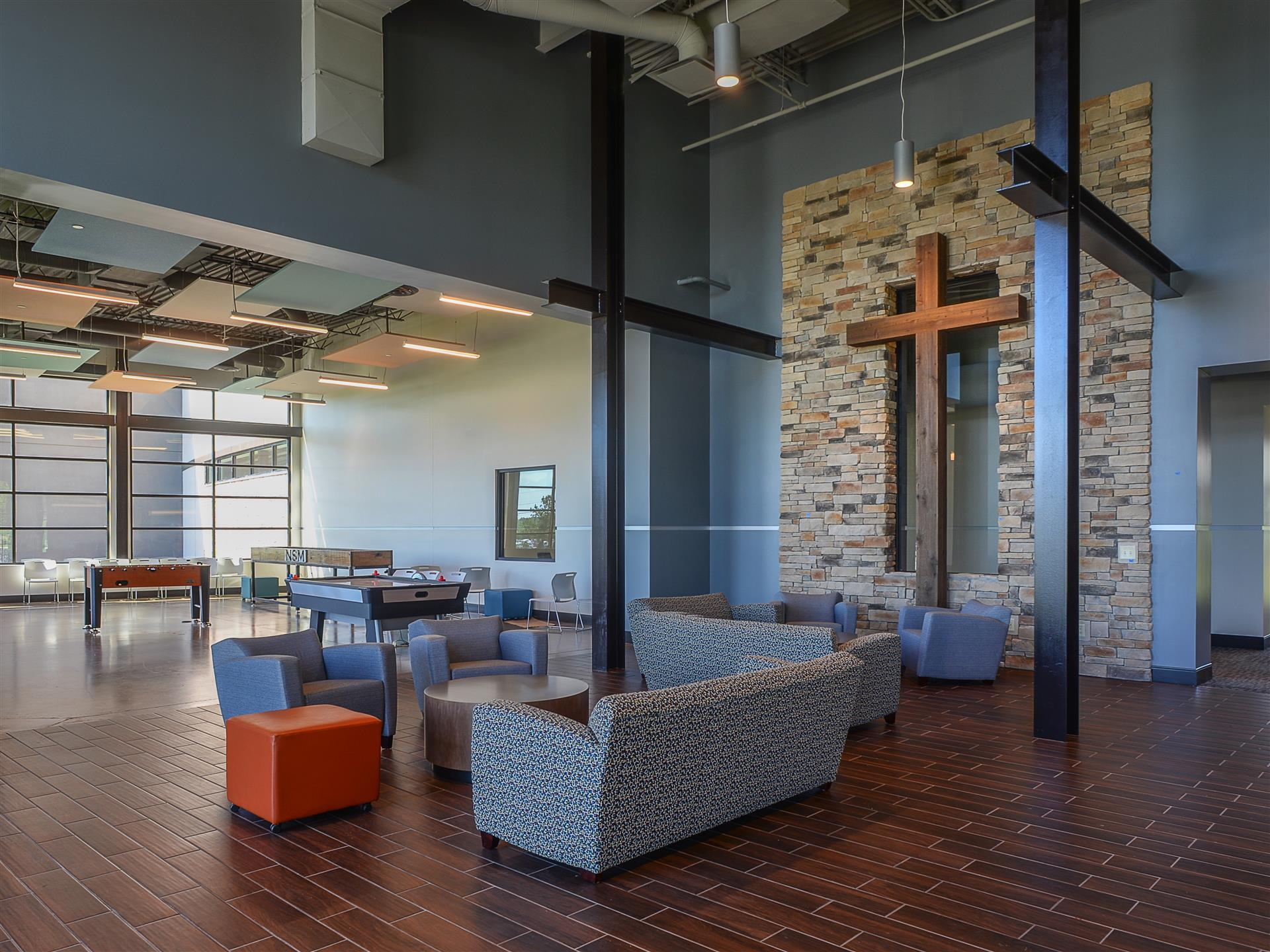 student gathering center with couches and cross on the wall