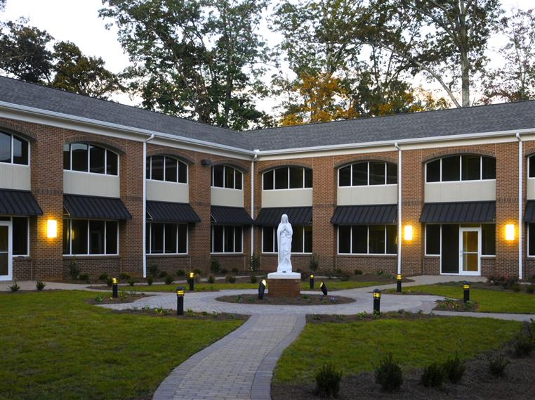 Exterior photo of 2-story housing for nuns and courtyard with statue in center
