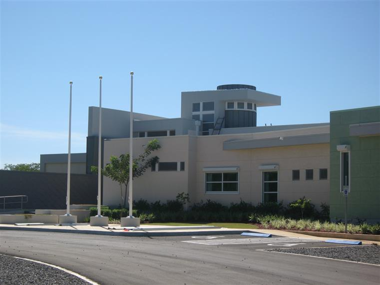 Government - Visitors' Center - yellow and green building with flag poles in front