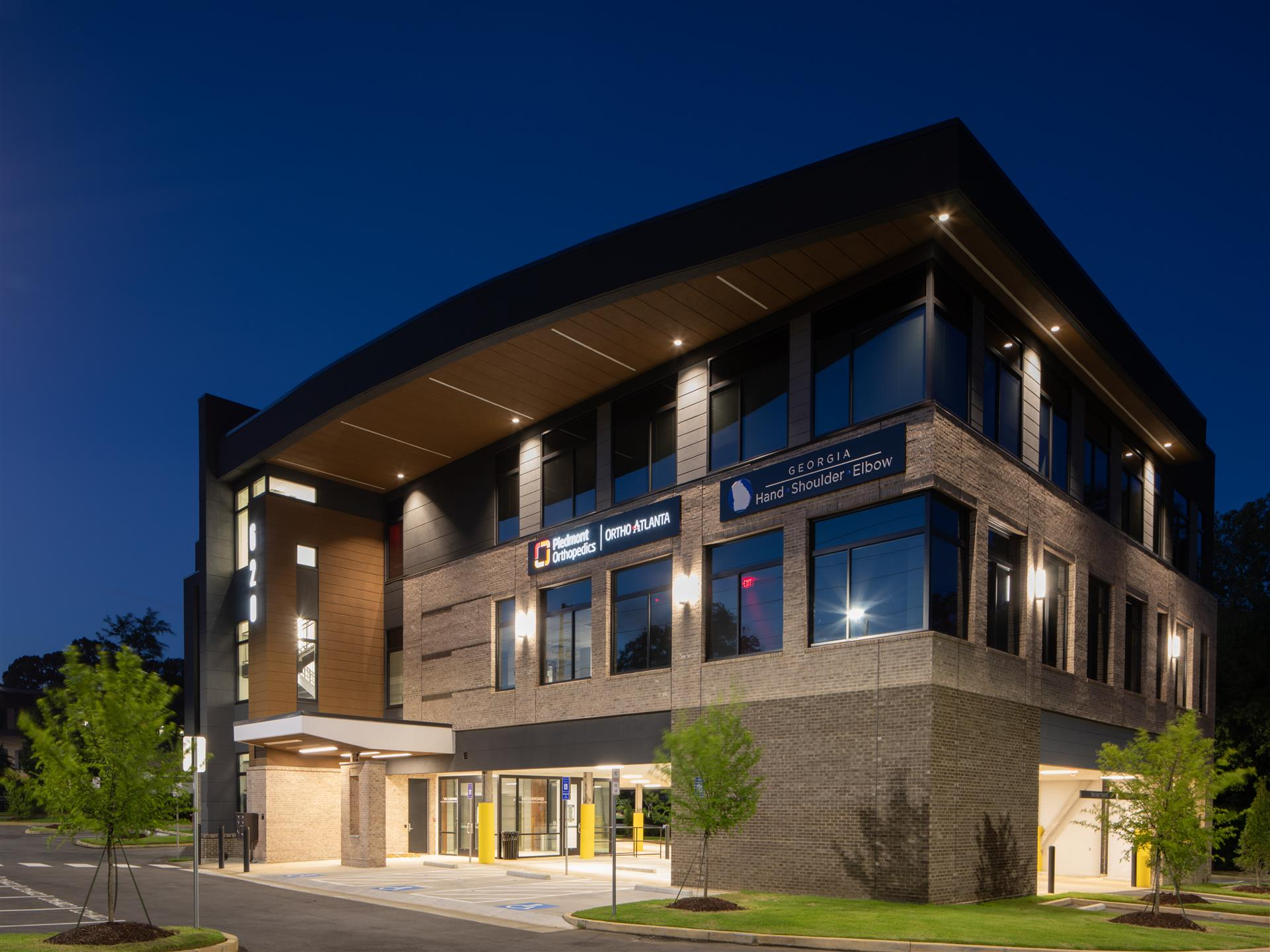 exterior photo of 2 story brick building with parking underneath, night shot