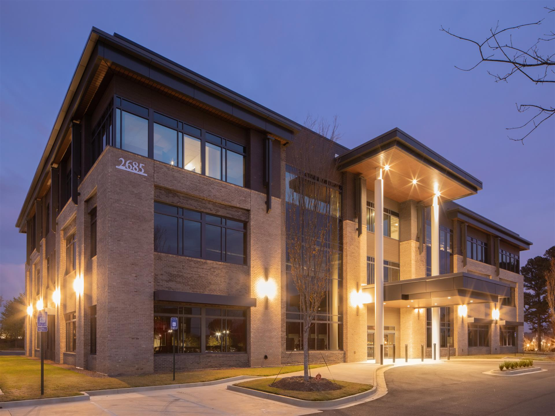 Night shot with exterior lights on for a 2 story building.  Lots of windows and 2-columns at the entrance