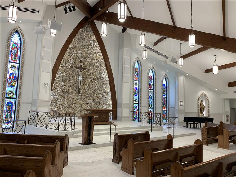 Interior of church shows pews, stain class windows, crucifix, pulpit