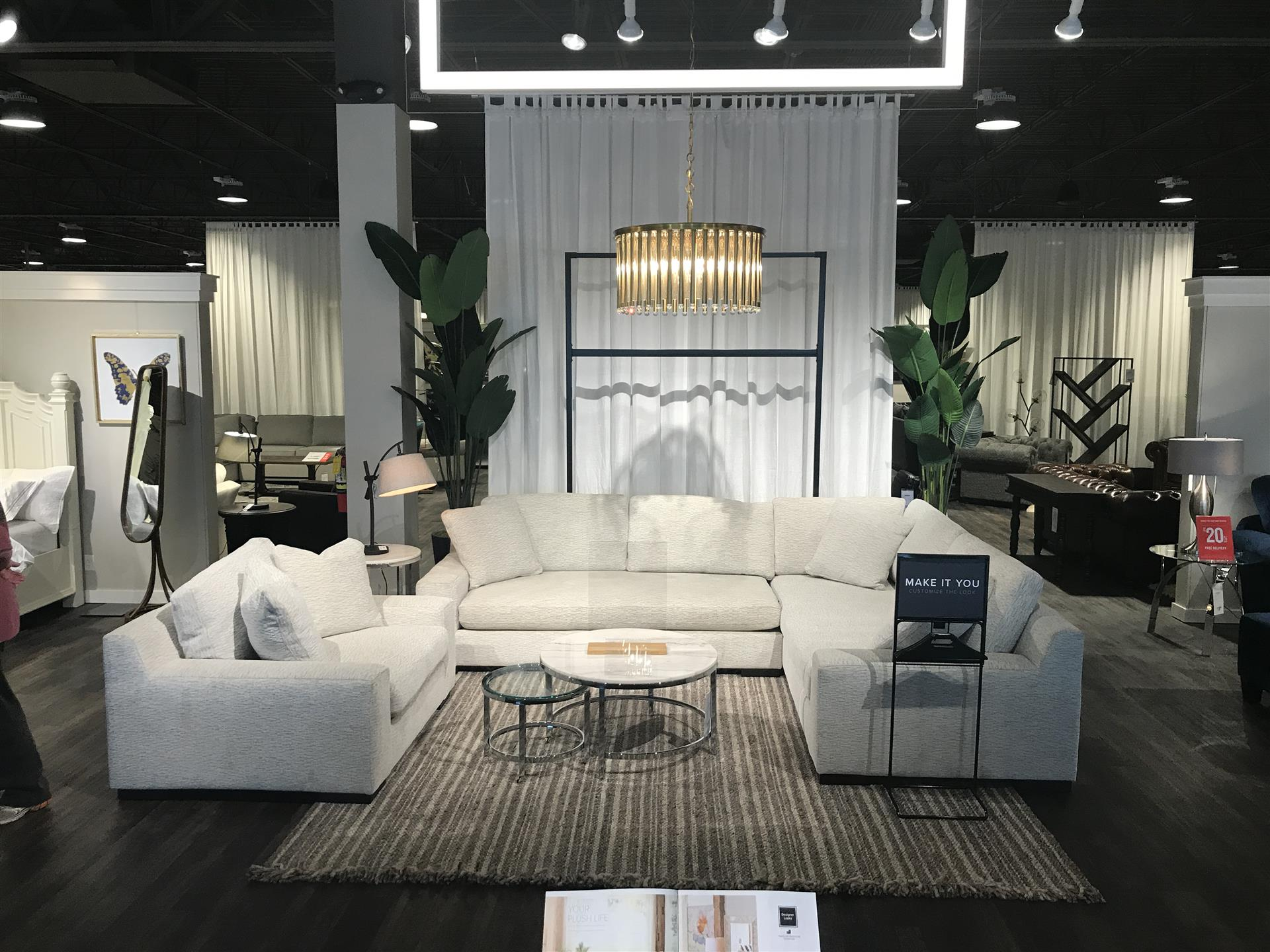 Furniture show room showing white  love seat and sofa with fixture overhead and lamp on side table, glasstop and marble circular coffee table in the middle