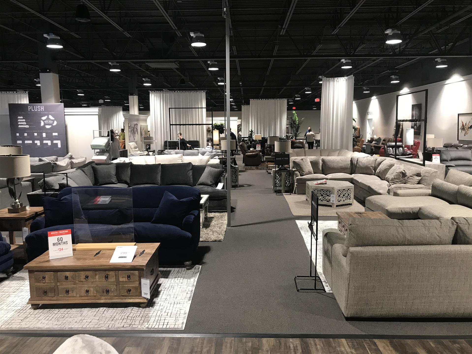 Vrious room set ups in a furniture store showing couches