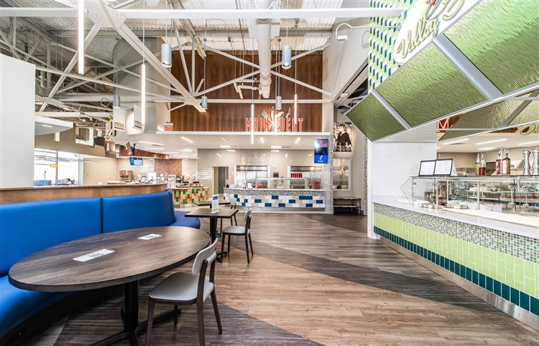 Dining hall for university.  Colorful, bright, hardwood floors, open ceiling with white fixtures