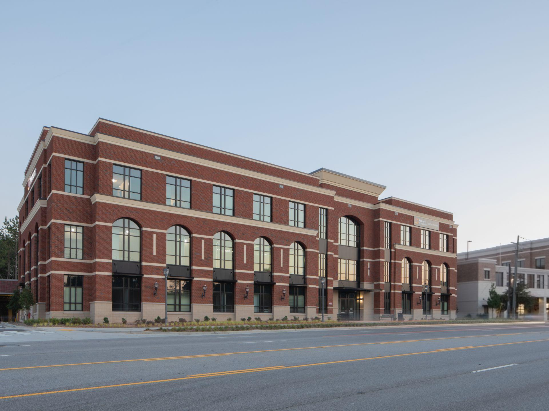 3-story brick building with arched windows on 2nd level.