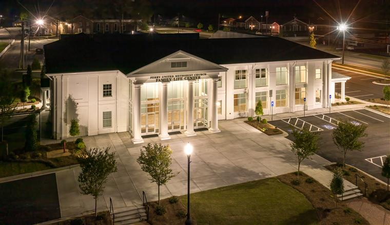 night shot of 2 story white building with columns