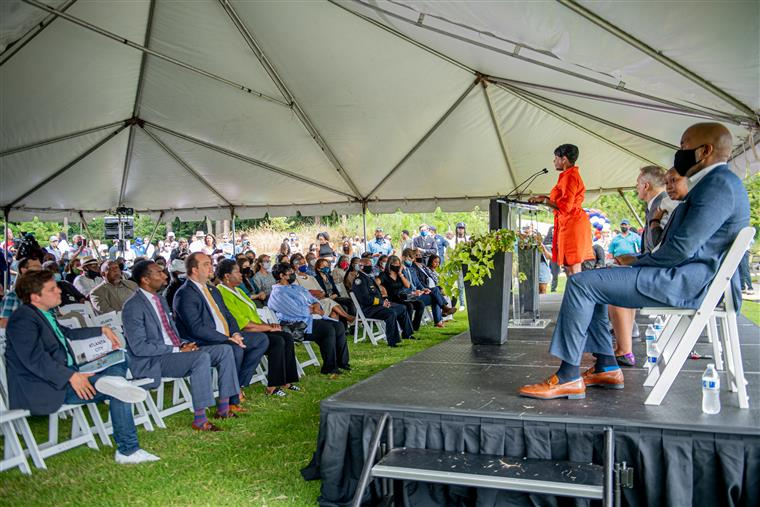 lady given speech in fromt of a large crowd under a tent.