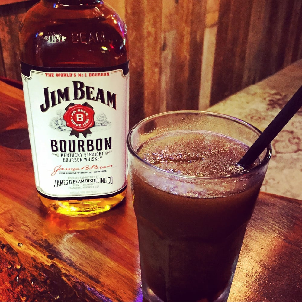 Beam and Coke in a glass next to a bottle of Jim Beam bourbon