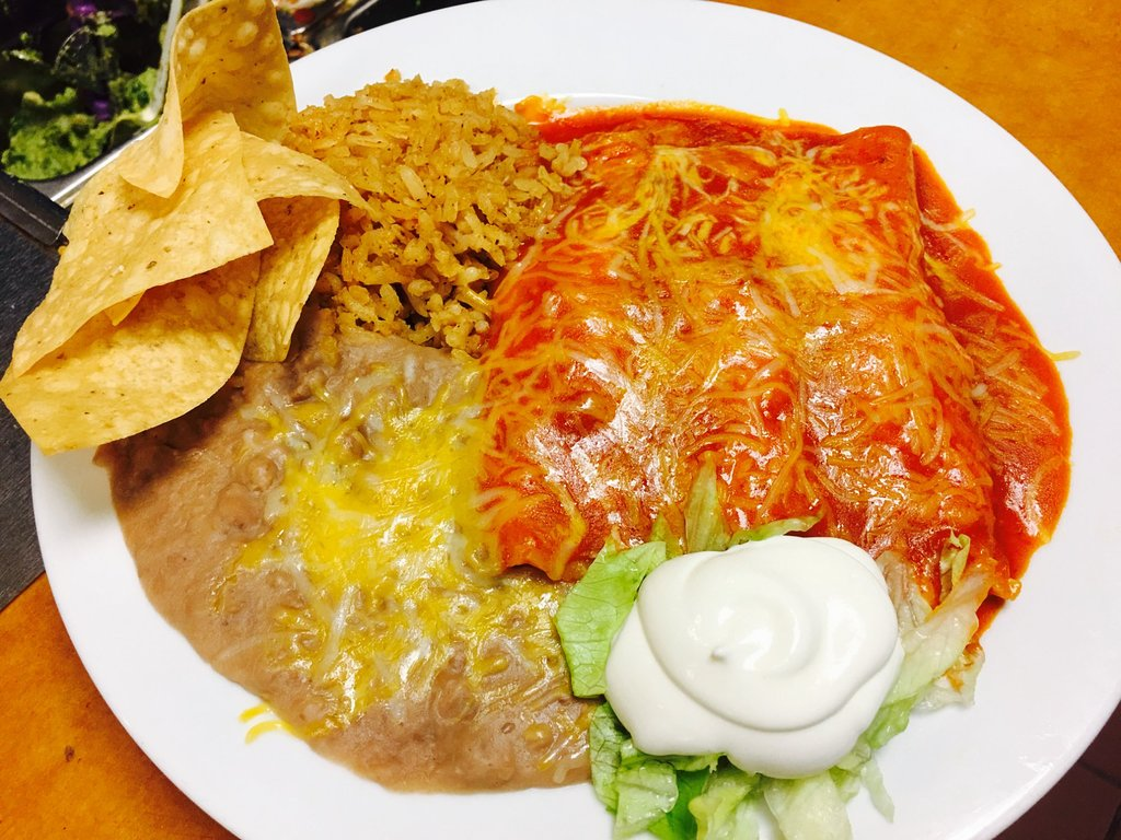 enchillada with rice and sour cream on a plate