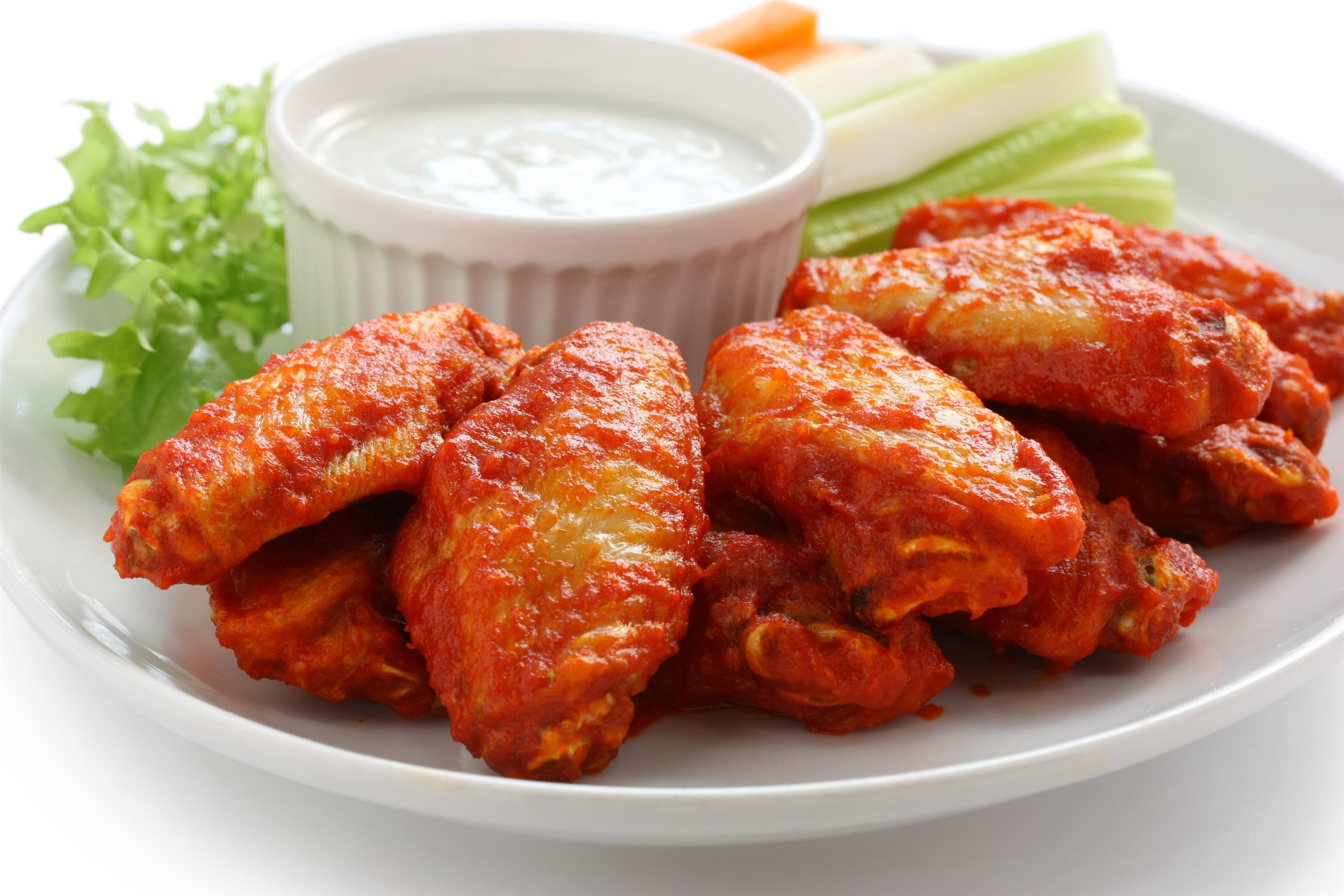 buffalo chicken wings on dish with celery, carrots, and ranch dressing in cup.
