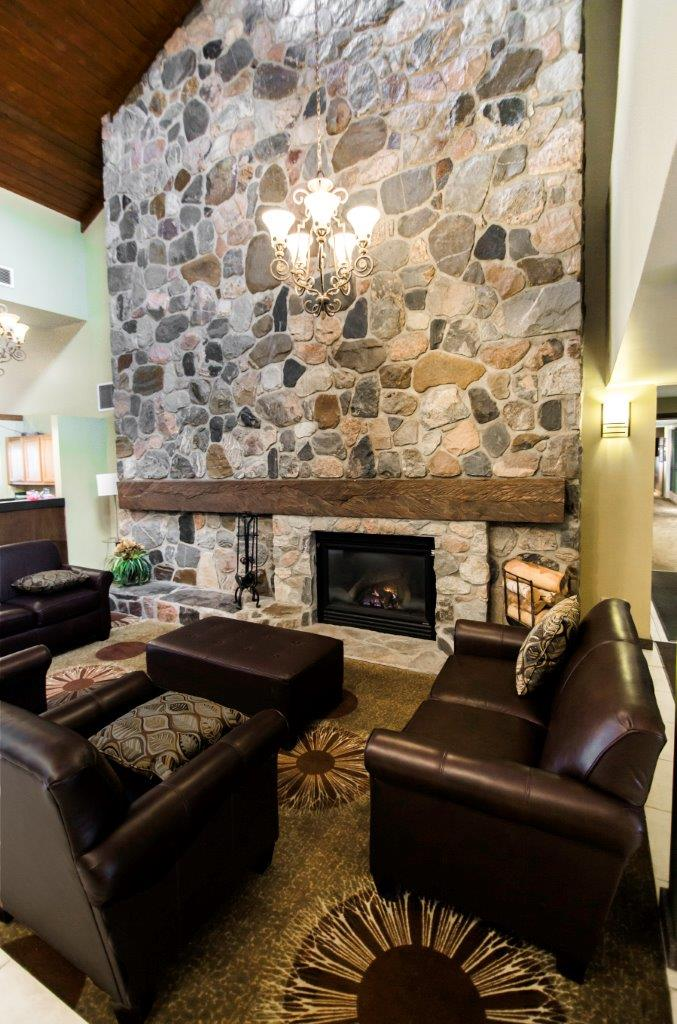 Lounge seat area in front of fireplace in tall, stone-patterned wall.