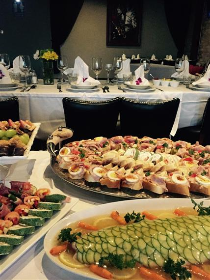 buffet table with trays of sandwiches and fruit