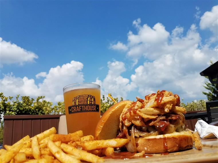 burger with fries and glass of beer outside on a table