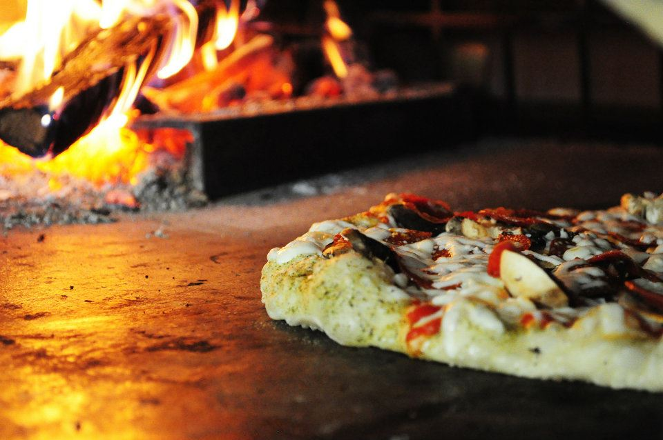pizza cooking in brick oven