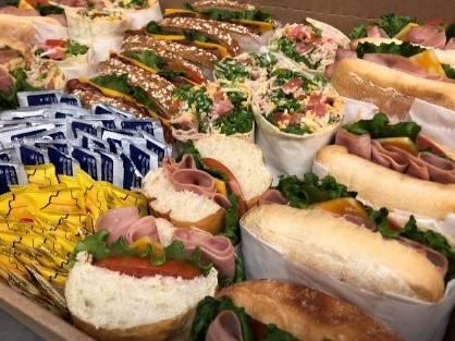 assortment of Sandwiches and wraps, including sides of mustard and mayo
