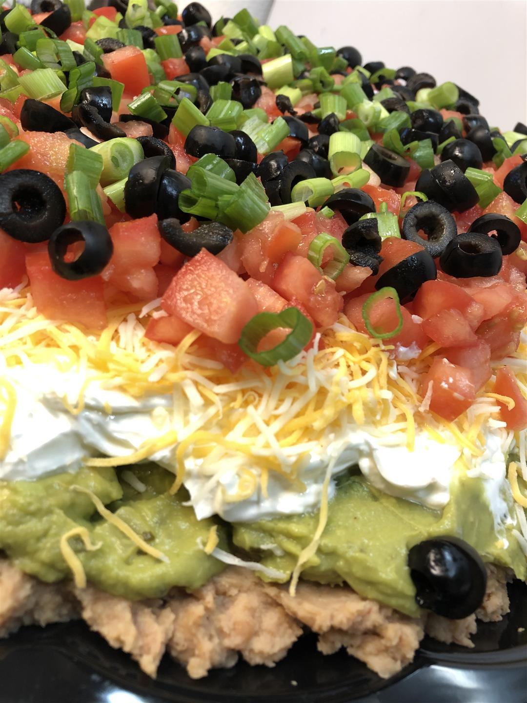 7 layer dip with refried beans, guacamole, sour cream, cheese, tomato, olives and green onions