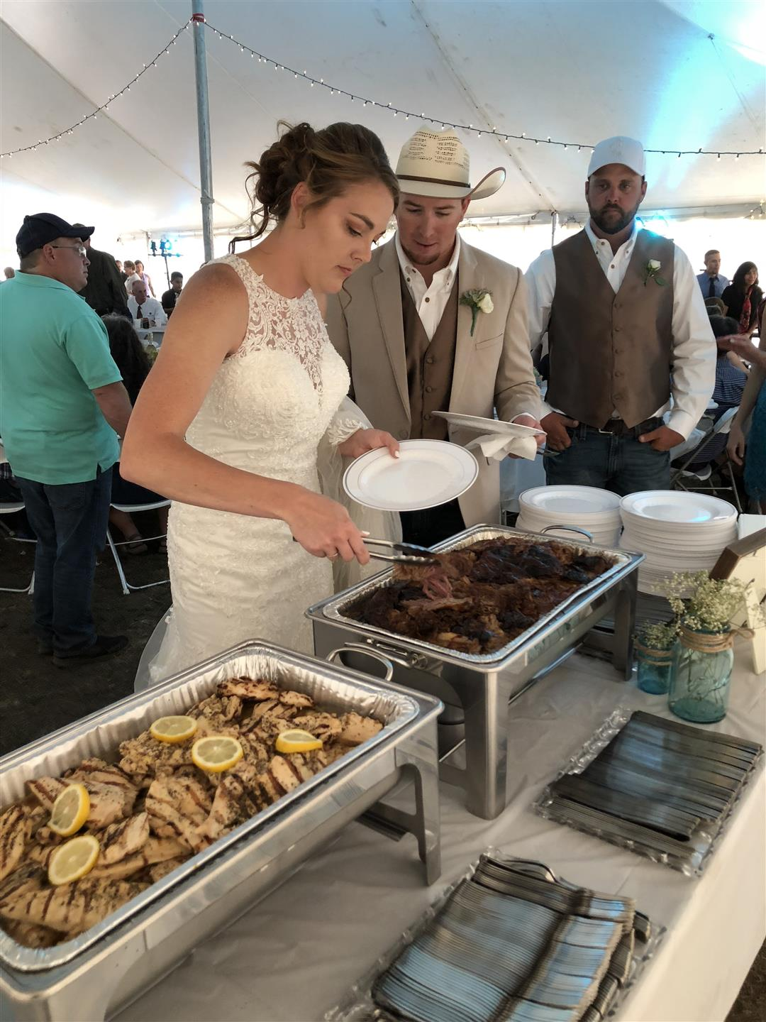 bride and groom helping themselves to buffet in reception tent